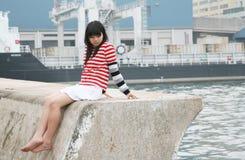 Muchacha asiática que desgasta sentarse colorido de las rayas Fotos de archivo