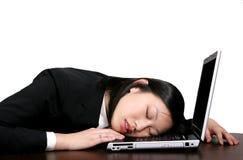 Muchacha asiática que duerme en el ordenador Foto de archivo