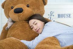 Muchacha asiática que duerme en la cama con un oso de peluche marrón grande Imagenes de archivo