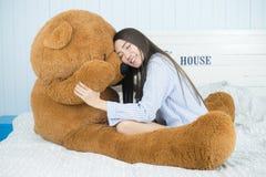 Muchacha asiática que duerme en la cama con un oso de peluche marrón grande Imagen de archivo libre de regalías