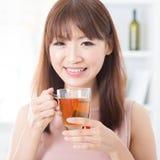 Muchacha asiática que goza de té fotografía de archivo