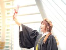 Muchacha asiática que gradúa con el diploma Foto de archivo libre de regalías