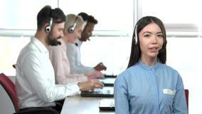 Muchacha asiática que habla con las auriculares metrajes