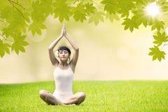 Muchacha asiática que hace yoga en el parque verde Imágenes de archivo libres de regalías