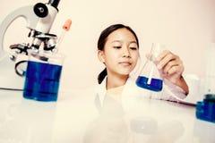 Muchacha asiática que juega como científico para experimentar Imagen de archivo