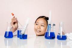 Muchacha asiática que juega como científico para experimentar con el equipo de laboratorio Fotografía de archivo