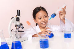 Muchacha asiática que juega como científico para experimentar con el equipo de laboratorio Fotos de archivo