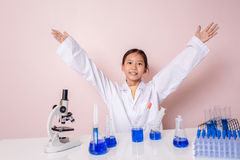 Muchacha asiática que juega como científico para experimentar con el equipo de laboratorio Foto de archivo libre de regalías