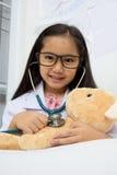 Muchacha asiática que juega como doctor Fotografía de archivo libre de regalías