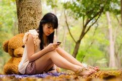 Muchacha asiática que juega el teléfono celular Imagenes de archivo