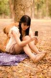 Muchacha asiática que juega el teléfono celular Imagen de archivo libre de regalías