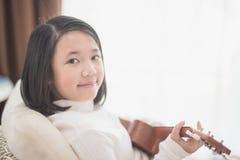 Muchacha asiática que juega el ukelele en Fotografía de archivo