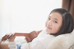 Muchacha asiática que juega el ukelele en Foto de archivo libre de regalías