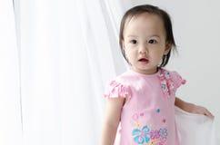 Muchacha asiática que juega la cortina blanca en casa foto de archivo