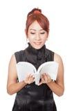 Muchacha asiática que lee un libro y una sonrisa Imágenes de archivo libres de regalías