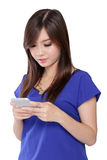 Muchacha asiática que manda un SMS con su teléfono elegante, aislado en blanco Imagenes de archivo