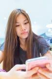 Muchacha asiática que mira su teléfono en café Imagen de archivo