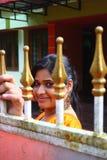 Muchacha asiática que mira a través de la puerta del metal Imágenes de archivo libres de regalías