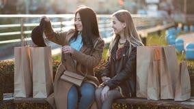 Muchacha asiática que muestra la última compra a su amigo metrajes