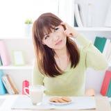 Muchacha asiática que piensa mientras que desayunando Imagenes de archivo
