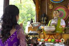 Muchacha asiática que ruega en templo Foto de archivo