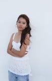 Muchacha asiática que se coloca delante de una pared blanca Fotos de archivo libres de regalías