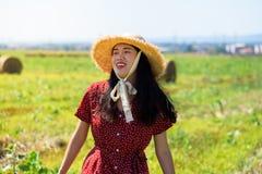 Muchacha asiática que se relaja adentro en un campo de trigo que lleva el vestido rojo fotografía de archivo