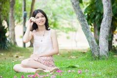 Muchacha asiática que se relaja en la hierba Imagenes de archivo