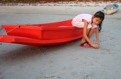 Muchacha asiática que se sienta en el pequeño barco rojo Fotografía de archivo libre de regalías