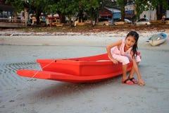 Muchacha asiática que se sienta en el pequeño barco rojo Imagenes de archivo