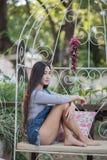 Muchacha asiática que se sienta en el sofá, relajándose Imagen de archivo libre de regalías