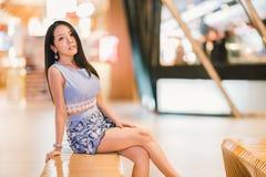 Muchacha asiática que se sienta en la alameda o los grandes almacenes de compras con el espacio de la copia Forma de vida moderna Fotos de archivo