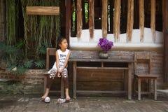 Muchacha asiática que se sienta en la silla delante de la casa del vintage fotografía de archivo