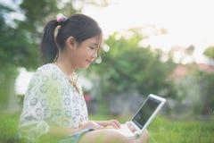 Muchacha asiática que se sienta en parque en la hierba verde con el ordenador portátil Foto de archivo