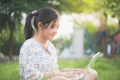 Muchacha asiática que se sienta en parque en la hierba verde con el ordenador portátil Imagenes de archivo