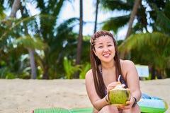 Muchacha asiática que se sienta por el océano que sonríe y que sostiene un coco imagen de archivo