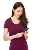 Muchacha asiática que sonríe mientras que usa su teléfono móvil Foto de archivo libre de regalías