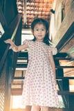 Muchacha asiática que sonríe y que viene abajo escaleras de madera en casa Vintag Imagen de archivo