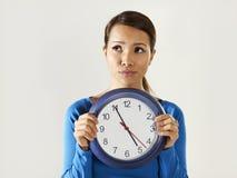 Muchacha asiática que sostiene el reloj azul grande con la tensión fotografía de archivo libre de regalías