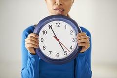 Muchacha asiática que sostiene el reloj azul grande con la tensión imagenes de archivo