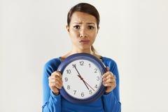 Muchacha asiática que sostiene el reloj azul grande con la tensión imágenes de archivo libres de regalías