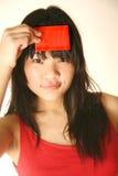 Muchacha asiática que sostiene la tarjeta roja en blanco imagen de archivo libre de regalías
