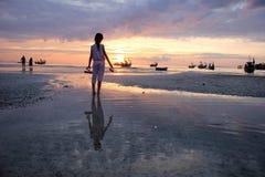 Muchacha asiática que sostiene los zapatos que miran puesta del sol en la playa Imagen de archivo libre de regalías