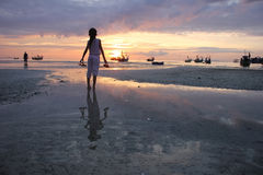 Muchacha asiática que sostiene los zapatos que miran puesta del sol en la playa Imagen de archivo