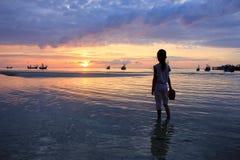 Muchacha asiática que sostiene los zapatos que miran puesta del sol en la playa Fotos de archivo libres de regalías