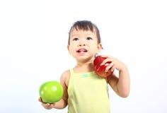 Muchacha asiática que sostiene manzanas Imagen de archivo