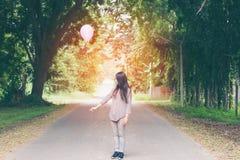 Muchacha asiática que sostiene un globo en el parque foto de archivo