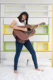 Muchacha asiática que toca la guitarra en dormitorio Foto de archivo libre de regalías