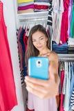 Muchacha asiática que toma el selfie del equipo en armario del dormitorio Foto de archivo libre de regalías
