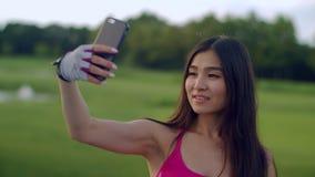 Muchacha asiática que toma el selfie en parque Selfie de la muchacha del deporte en el teléfono en parque almacen de metraje de vídeo